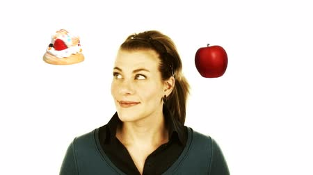 jabłka : woman hesitating between the treat of a fattening cake and a healthy apple. Wideo
