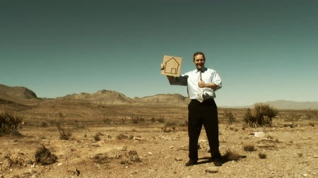 perdido : One single businessman in the middle of the desert holding a cardboard sign with an home logo on it Vídeos