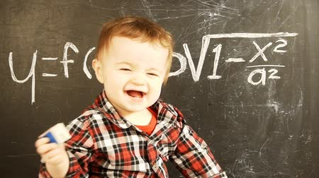 infant formula : Adorable baby boy in front of a blackboard with a scientific formula