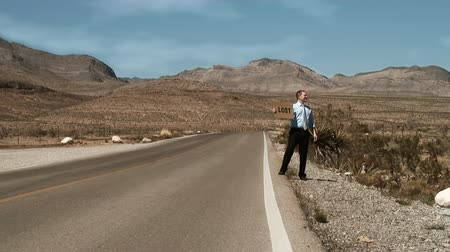 perdido : One single man on a desert empty road holding a carboard sign with LOST  on it Vídeos