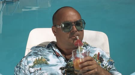 pieniądze : video of a man having a drink by his swimming pool and truly enjoying is vacation
