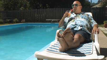 zengin : video of a man having a drink by his swimming pool and truly enjoying is vacation