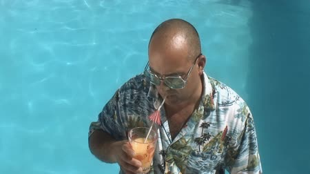 żart : video of a man having a drink by his swimming pool and