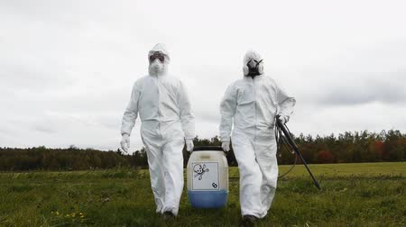 tehdit : Two man in protective suit carrying dangerous chemical