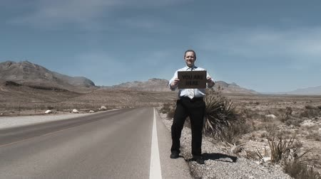 znak : One single man on a desert empty road holding a cardboard sign with YOU ARE HERE written  on it
