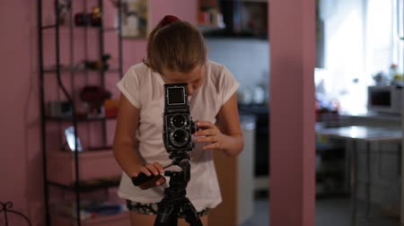 een girl looks into the mine of a medium format camera aimed at us, taking picture of you.