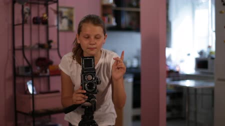 teen girl looks into the mine of a medium format camera aimed at us, taking picture of you.