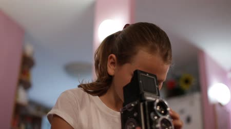 aimed : teen girl looks into the mine of a medium format camera aimed at us, taking picture of you.