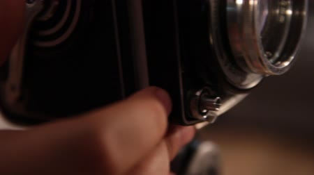 index finger presses the shutter button of a vintage medium format camera.