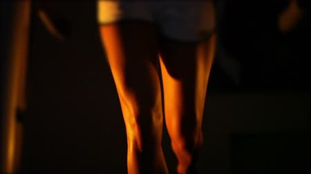 beautiful tanned female legs run on a treadmill in the dark.