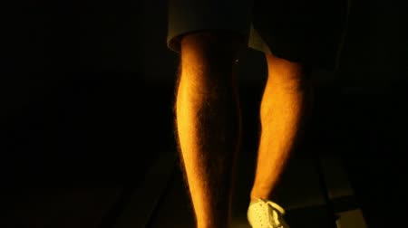 man walking on a treadmill in the dark. close-up of legs.