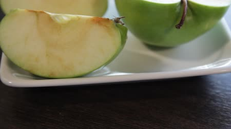 mozog e fel : slices of green apple on a square white plate. the camera moves around this to the left. close-up. macro Stock mozgókép