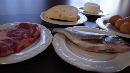 high protein foods. raw meat and fish, cheese, eggs on separate plates. the camera moves around this to the right