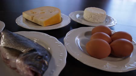 high protein foods. raw meat and fish, cheese, eggs on separate plates. the camera moves around this to the left