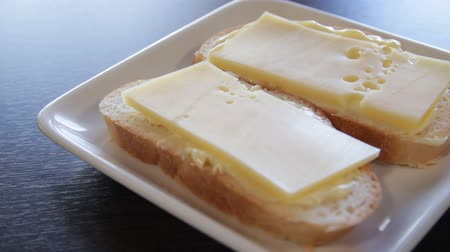 mozog e fel : 2 white bread sandwiches with butter and cheese on a plate. the camera moves around this to the right. close-up
