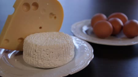 fehérjék : high protein foods. cheese and eggs on separate plates. the camera zooms in on it Stock mozgókép