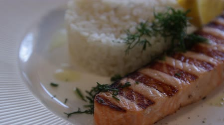 mozog e fel : grilled red fish, served with rice and lemon. high protein foods. the camera moves around this to the right. close-up