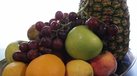 Pineapple, apple, red grapes, lemon, orange. the camera moves around this to the right. close-up