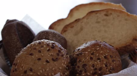 the camera moves around the basket with several kinds of bread. close-up Stockvideo