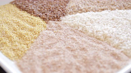 mozog e fel : several types of cereals on one plate. buckwheat, rice, millet, barley. close-up. the camera moves around this to the left