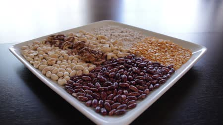 plate on which dry red beans and yellow peas and various nuts.the camera moves around this to the right