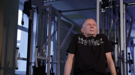 positive ageing : A man of the age performs joint gymnastics for the shoulders in the gym.Shoulder rotation.Glide cam footage