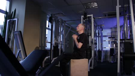 A man of the age performs joint gymnastics for the elbows and back in the gym.Spinal curvature.Copy space. Stockvideo