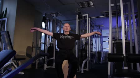 positive ageing : A man of the age performs joint gymnastics for the wrist in the gym.wrist rotation.Copy space. Stock Footage