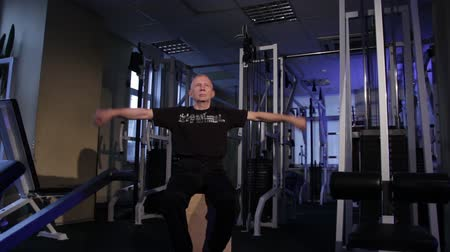 istikrar : A man of the age performs joint gymnastics for the arms in the gym.Forearms rotation.Copy space. Stok Video