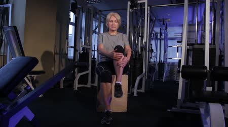 positive ageing : Knee-to-chest rises alternately in a sitting position.An older woman practicing joint gymnastics.Copy space. Stock Footage