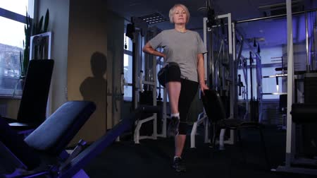 positive ageing : an older woman doing knee-lifts standing up.practicing joint gymnastics.Copy space.front view.glide cam footage Stock Footage