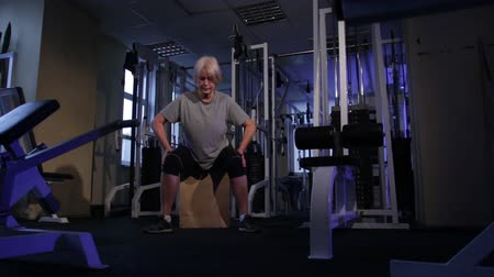 positive ageing : Elderly woman performs isometric exercise, kneeling to the sides and back.front view.Copy space Stock Footage