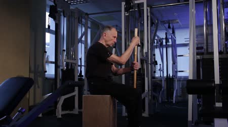 positive ageing : isometric exercise with a stick.an elderly man holds a stick vertically in front of him in a sitting position.Copy space.