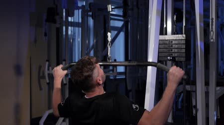 Lat pulldown.A young man does a back muscle exercise on a simulator.copy space