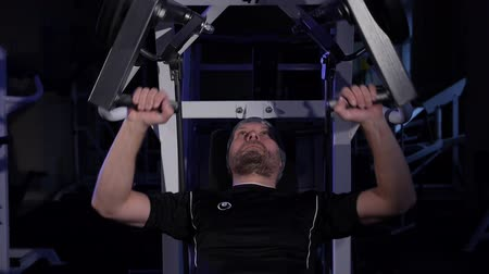 A young man makes a Bench press on a simulator.low key frame