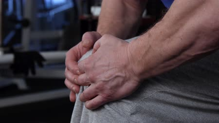 positive ageing : Powerful athlete makes isometric exercise by resisting kneeling with his hands.side view.close-up Stock Footage
