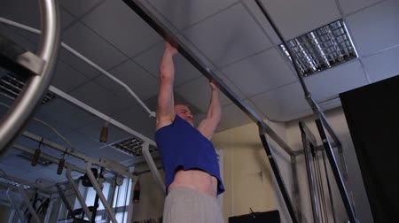 positive ageing : a powerful athlete of age performs a planche on a bar