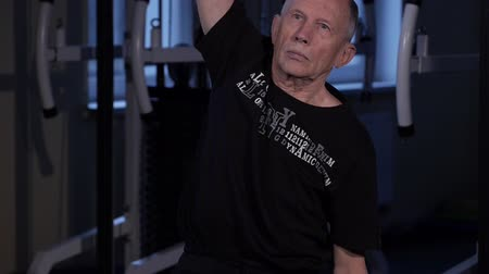 вертикально : A man of the age performs joint gymnastics in the gym.Raising the arm vertically upwards and tilting the torso sideways.Close-up