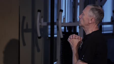 positive ageing : A man of the age performs joint gymnastics for the elbows and back in the gym.Spinal curvature.Close-up Stock Footage