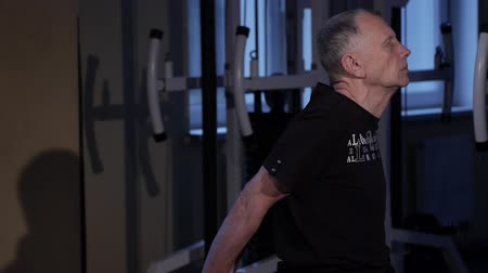 positive ageing : A man of the age performs joint gymnastics for the back in the gym.Straightening of the arms behind the back.Close-up