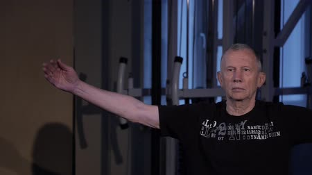 стабильность : A man of the age performs joint gymnastics for the wrist in the gym.wrist rotation.Copy space Стоковые видеозаписи