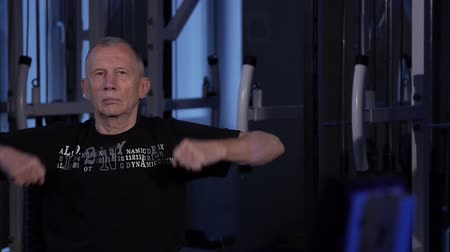 tartózkodás : A man of the age performs joint gymnastics for the arms in the gym.forearms rotation.Copy space