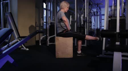 Extension of the legs at the knees in a sitting position.An older woman practicing joint gymnastics.Copy space.side view