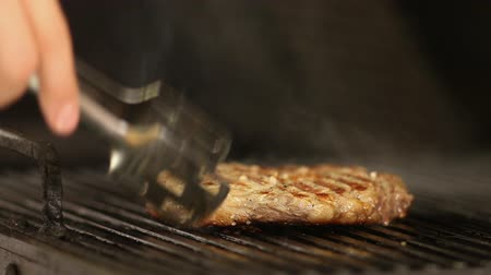 alicate : the chefs hand turns the beef steak on the grill with pliers.close-up