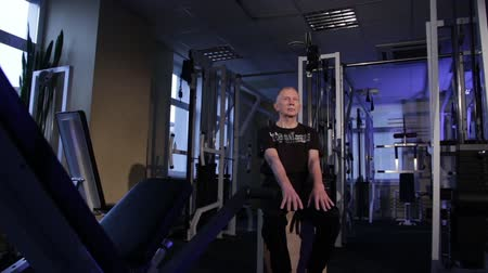 positive ageing : A man of the age performs joint gymnastics for the fingers in the gym.Clenching and unclenching your fist, arms out in front of you downstairs.Copy space.