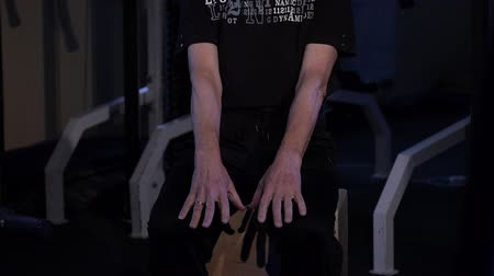 positive ageing : A man of the age performs joint gymnastics for the fingers in the gym.Clenching and unclenching your fist, arms out in front of you downstairs.Copy space