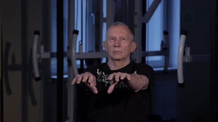 positive ageing : A man of the age performs joint gymnastics for the fingers in the gym.Clenching and unclenching your fist, arms out in front of you.Copy space