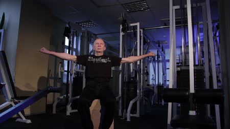 positive ageing : A man of the age performs joint gymnastics for the fingers in the gym.Clenching and unclenching your fist, arms extended left and right.Copy space