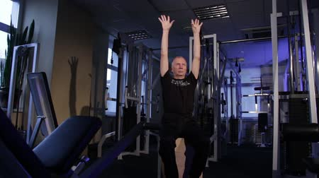 positive ageing : A man of the age performs joint gymnastics for the fingers in the gym.Clenching and unclenching your fist, hands up.Copy space. Stock Footage