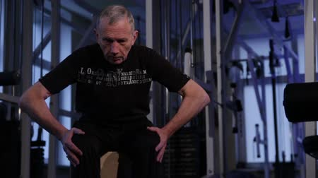 move well : An elderly man performs isometric exercise, kneeling to the sides.front view.Copy space